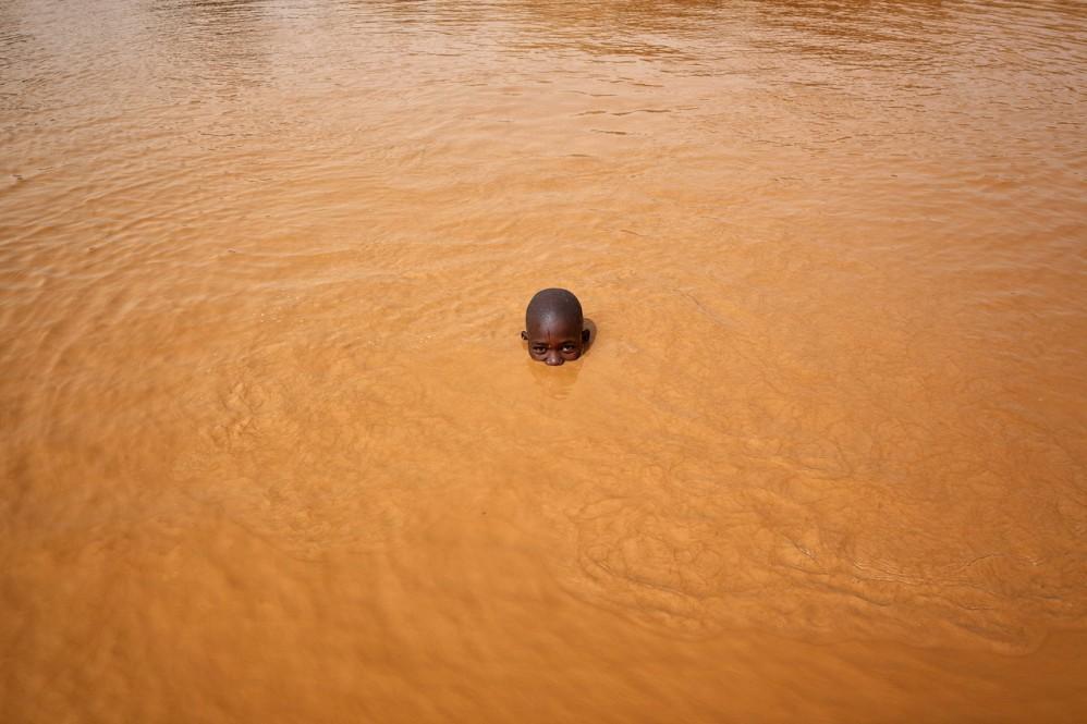 Abdul Haruna, 14 anni, è uno dei tanti bambini che lavorano in miera. Qui mentre si lava in acqua dopo uuna giornata di lavoro a luglio - foto di Matjaz Krivic